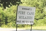 A sign advertising molasses production.
